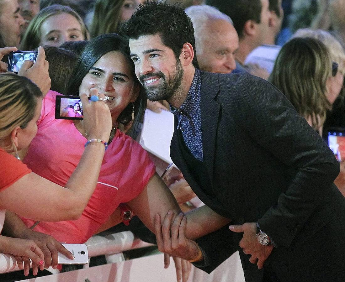 El actor Miguel Ángel Muñoz posa para una foto con una admiradora a su paso por la alfombra roja de San Sebastián