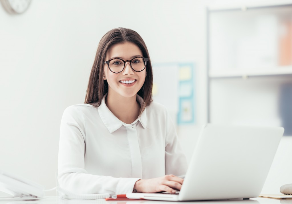 Young woman working at office desk, she is typing on a laptop and smiling, job and career concept