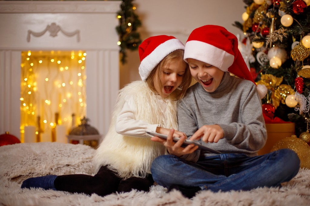 Amazed boy and girl in Christmas hats sitting near brightly decorated Christmas tree and using tablet.