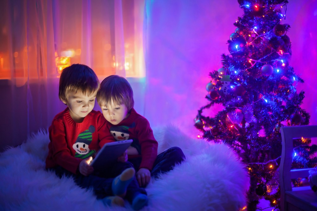 Two boys, playing on tablet at home, next to christmas tree in the evening