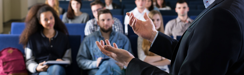 Young students listening the lecture with interest on university. Close-up of young professor's hands